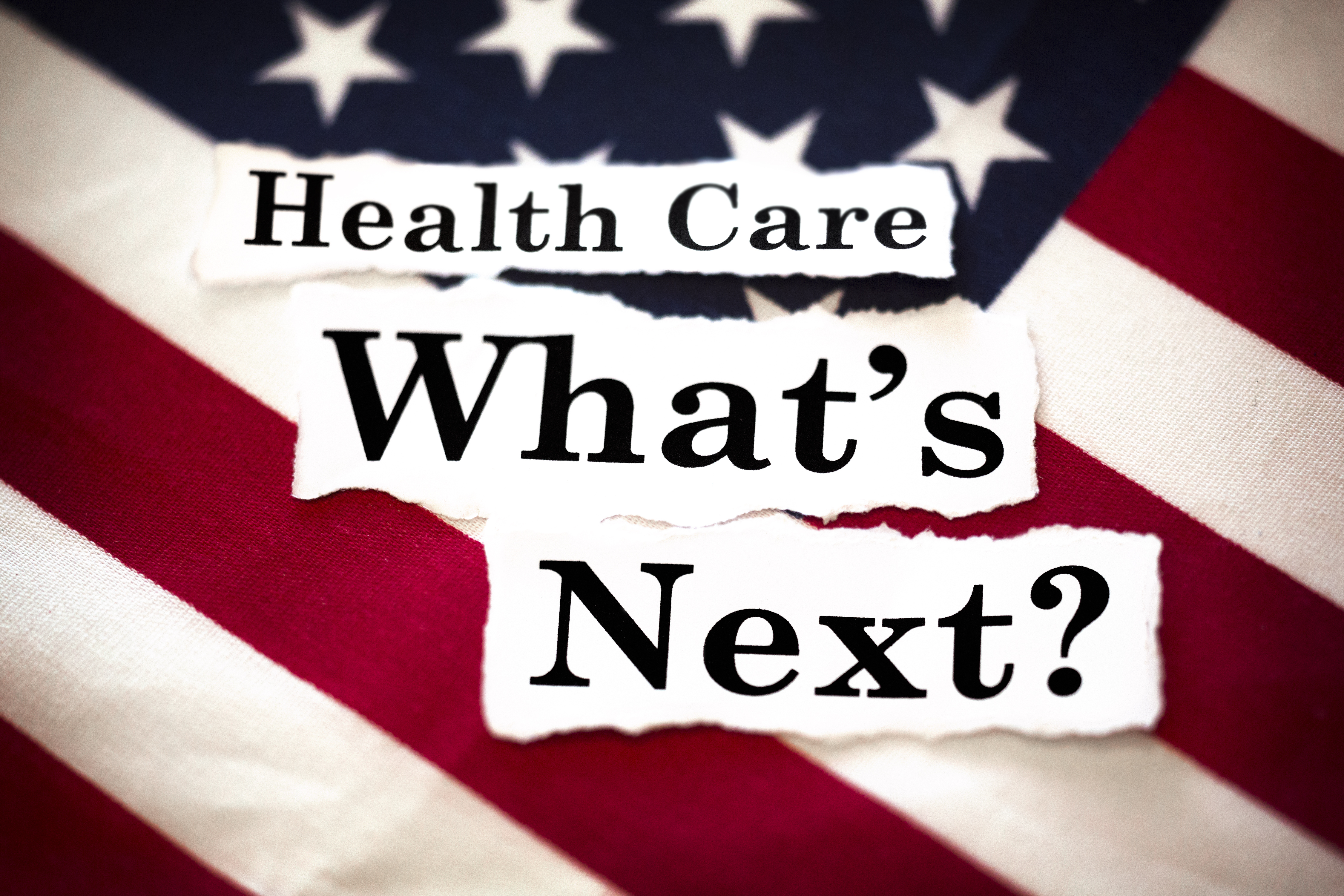 "The words ""Health Care What's Next?"" with an American flag in the background."